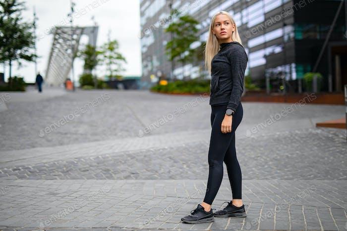 Beautiful urban scandinavian woman in workout outfit standing in city