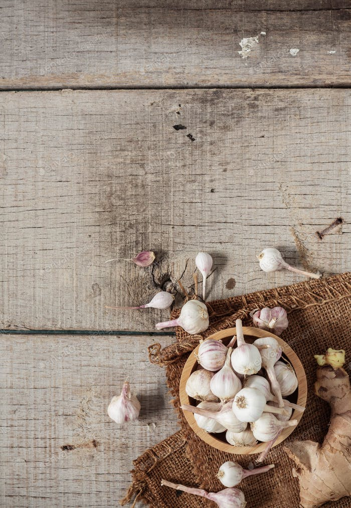 Garlic in bowls on wooden floor