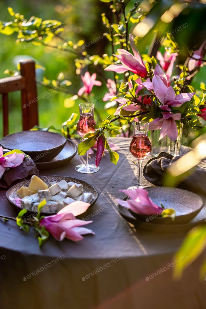 Beautiful table setting in garden on sunset light