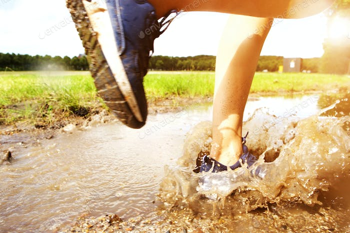 Runner's sneakers splashing in mud puddle