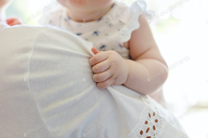 Small baby girl holding the hand on mother's shoulder
