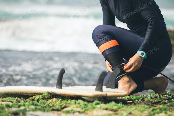 Surfer tying leg leash before surfing