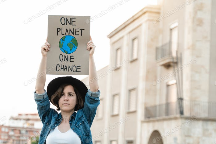 Young demonstrator activist holding banner during climate change protest outdoor in the city
