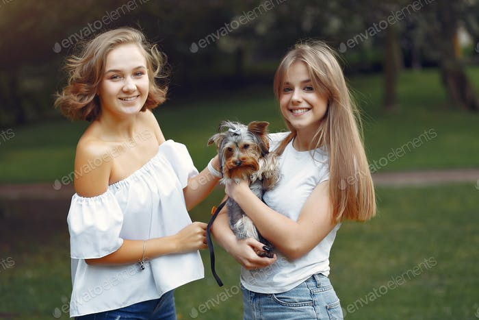Two cute girls in a park playing with little dog