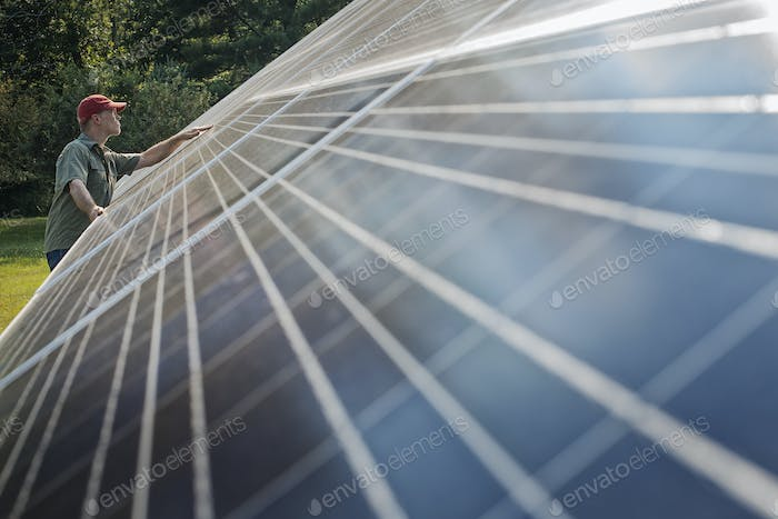 A man inspecting the surface of a large tilted solar panel.