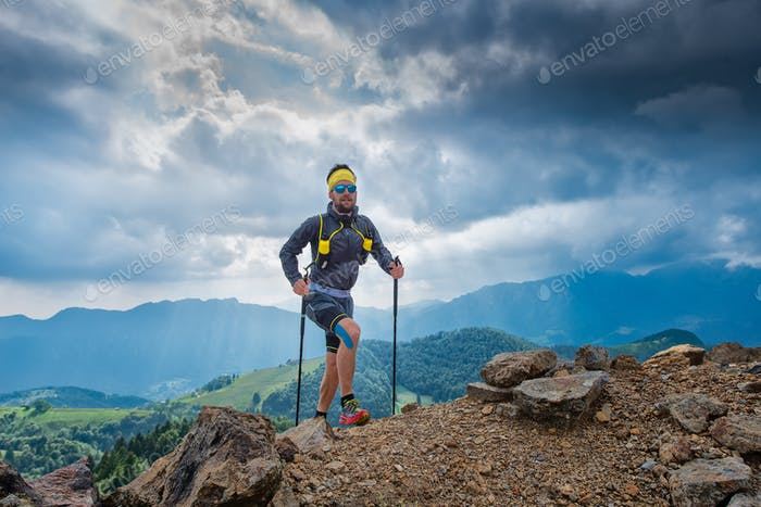 Male athlete goes up to a mountain behind panorama of mountains
