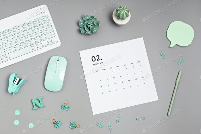 Desktop with calendar for february and office supplies