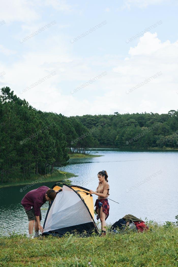 Couple assembling tent