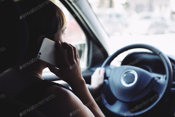 Woman in the car talking on mobile phone while driving