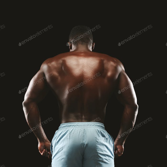 Unrecognizable afro sportsman showing athletic back on black background