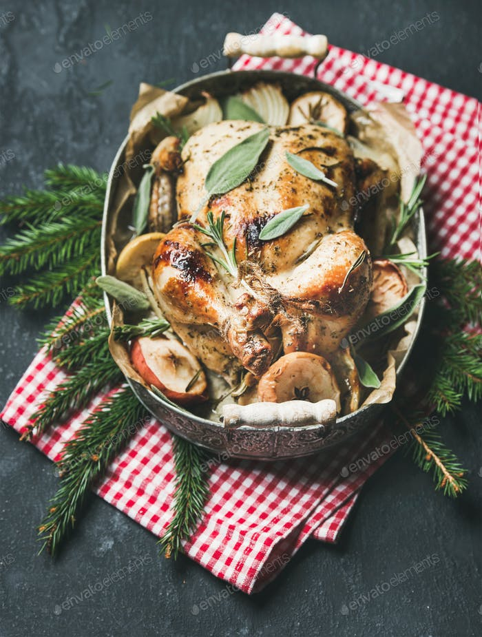 Oven roasted whole chicken in tray with Christmas table decotarion