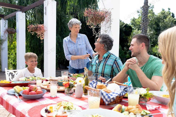 Caucasian family sitting at table during a family lunch in the garden