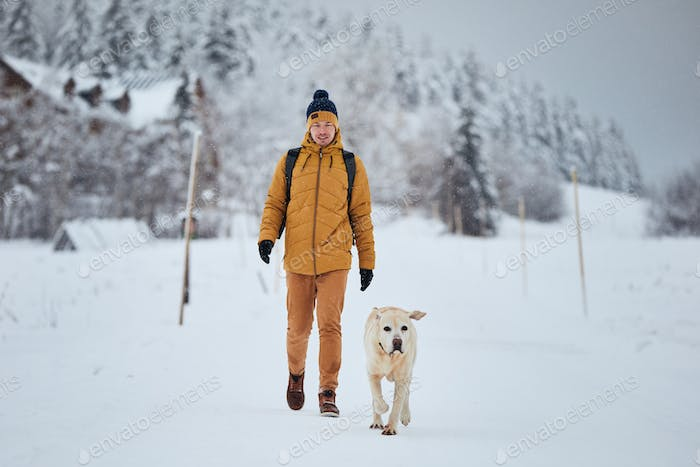 Front view of young man with dog in winter