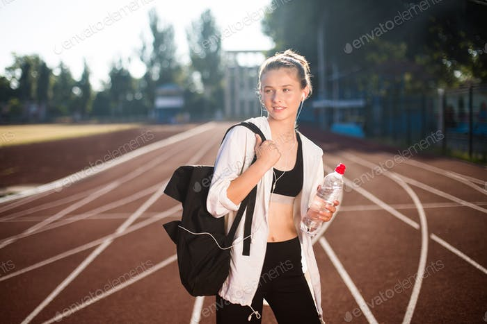 Pretty girl in sporty top and legging dreamily looking aside after training on running track