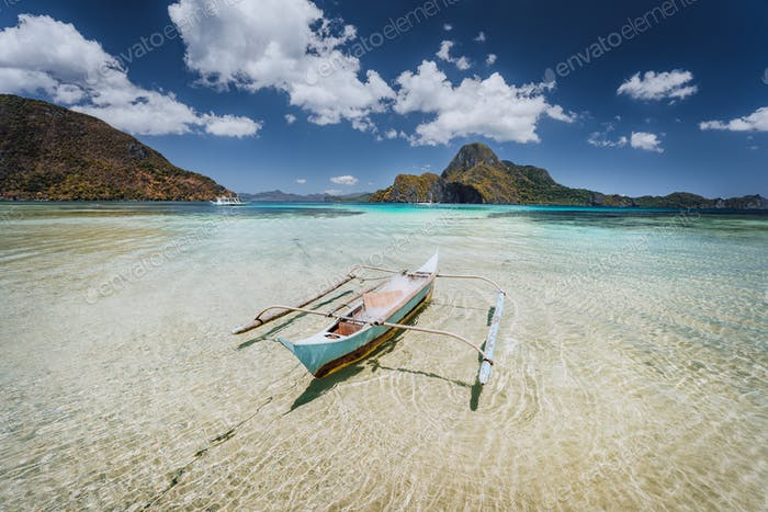 Traditional filippino fishermen banca boat in blue tropical lagoon at El Nido bay with Cadlao Island