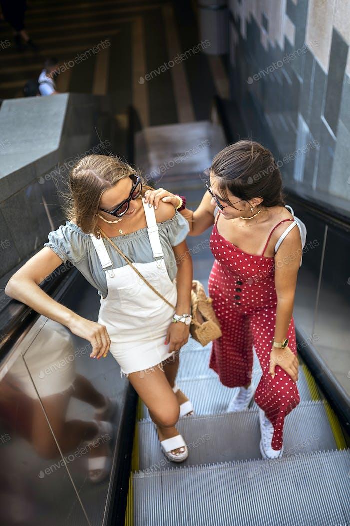 Lächelnde weibliche Freunde klettern Rolltreppe