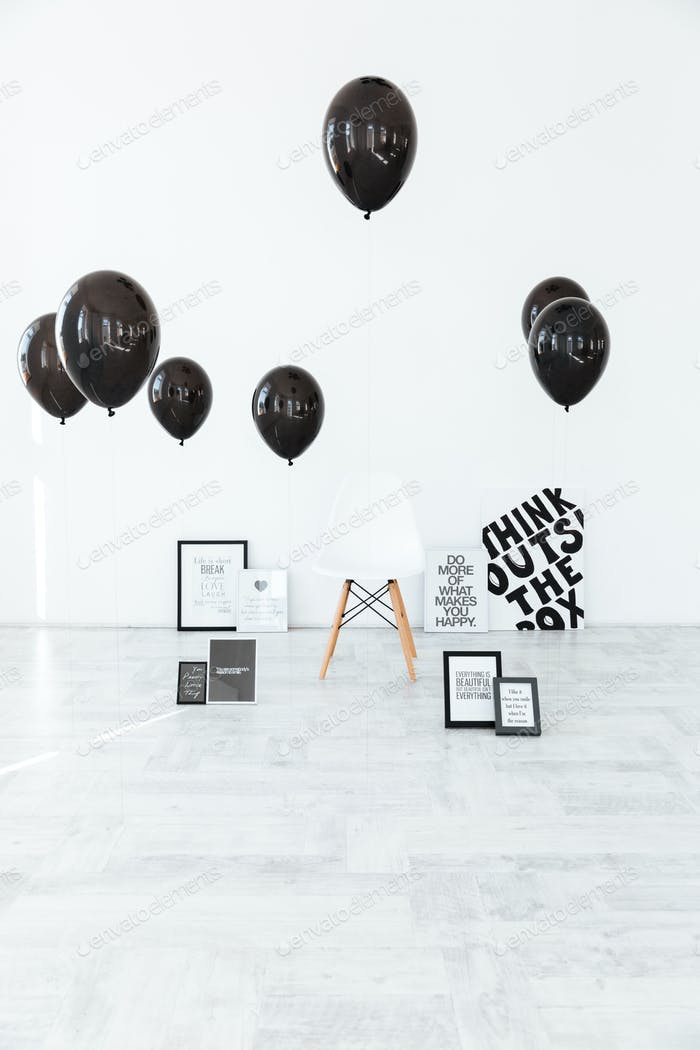 Studio decorations of chair, posters and black balloons