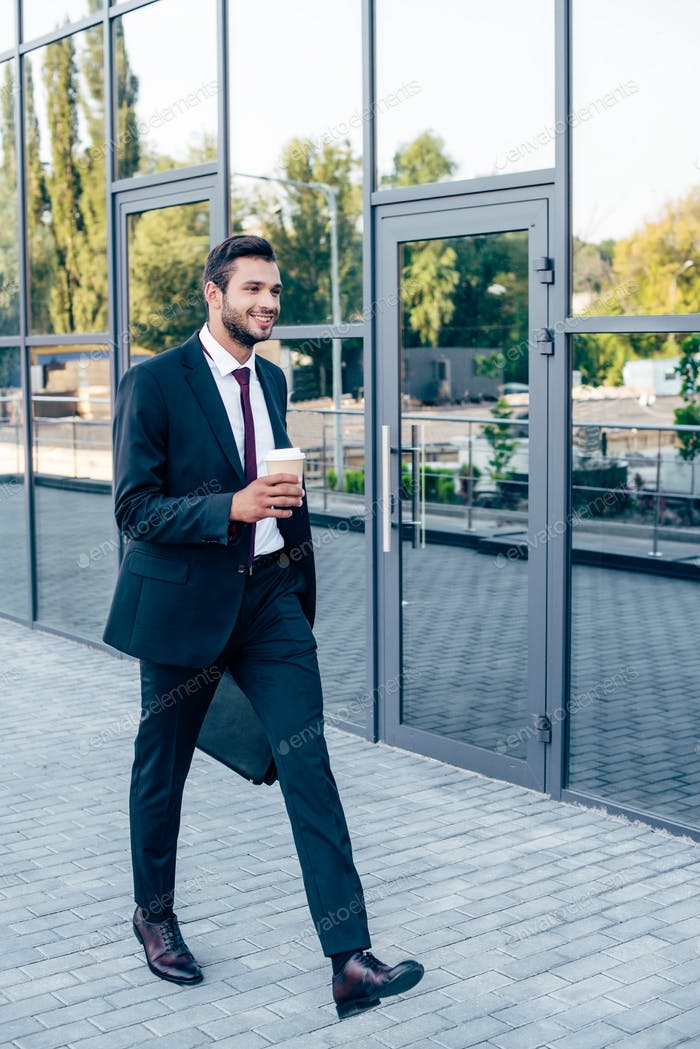 happy young businessman walking with coffee to go