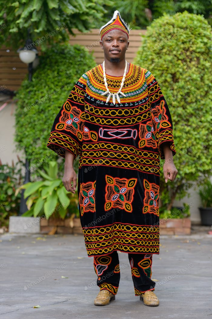 Full body shot of young African man wearing traditional clothing outdoors