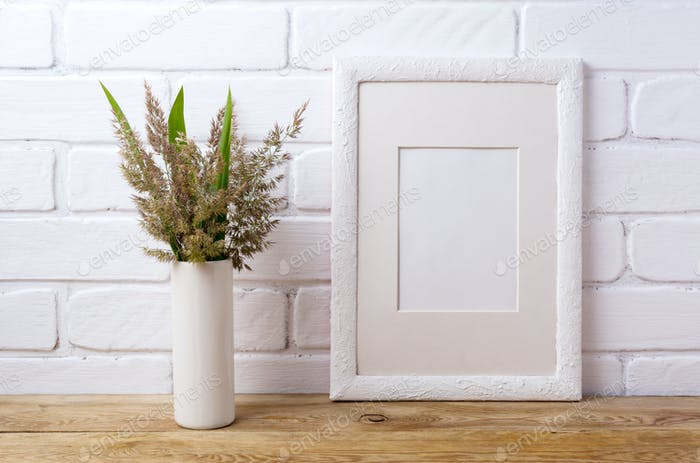 White frame mockup with grass and green leaves in cylinder vase