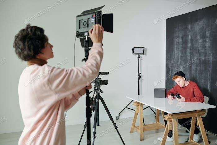 Junger Mann in Freizeitkleidung Vorbereitung Video amera vor dem Dreharbeiten im Studio