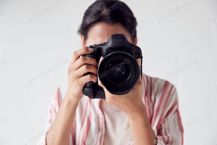 Female Photographer With Camera On Photo Shoot Against White Studio Backdrop