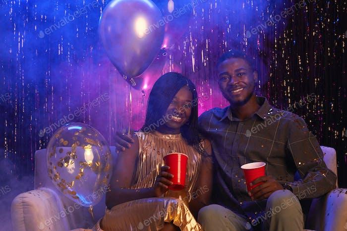 Улыбающаяся афро-американская пара позирует на вечеринке