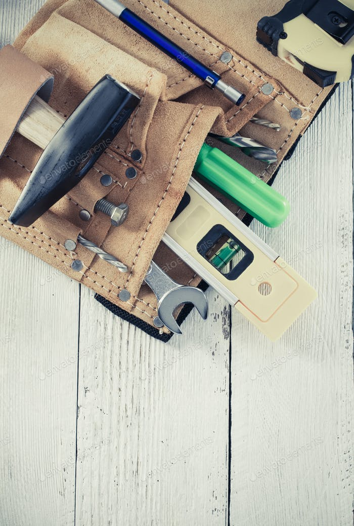 tools and instruments in belt on wood