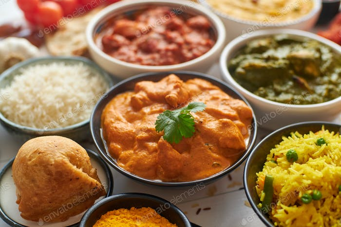Various Indian dishes on a table. Mild butter chicken in caramic bowl