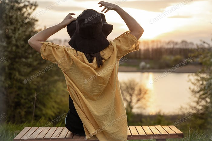 A stylishly woman sits on a bench and looks into the distance at the sunset.