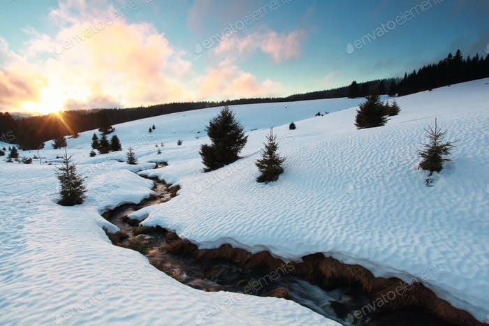 winter sunset over snow mountains with river