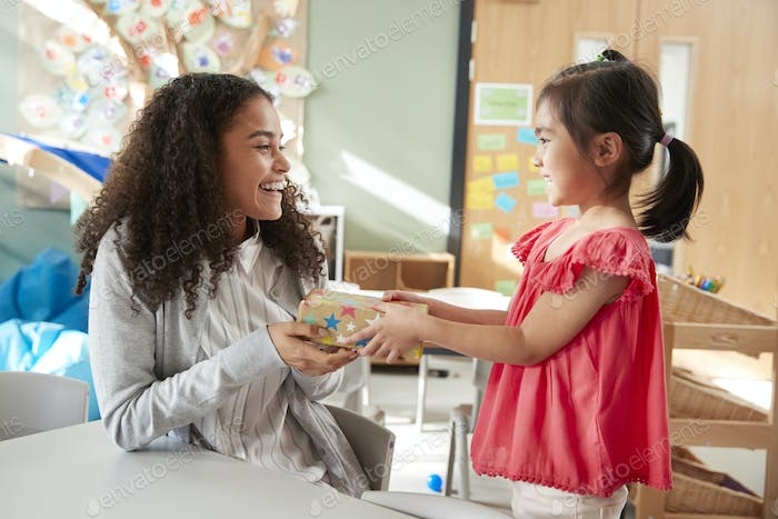 Kindergarten schoolgirl giving a gift to her female teacher in a classroom, side view, close up