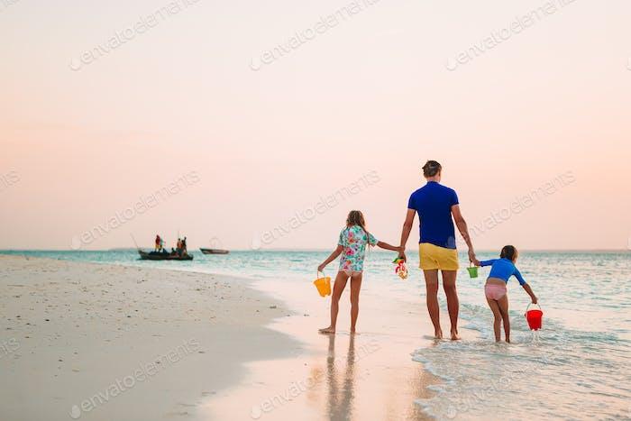 Glücklicher Vater und seine entzückenden kleinen Töchter am tropischen Strand mit Spaß