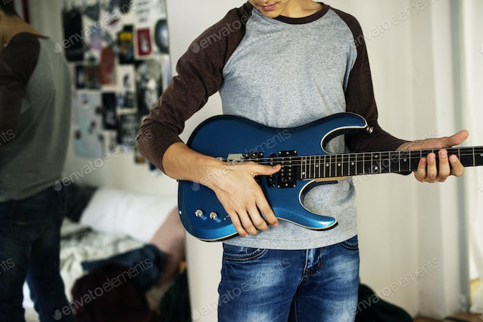 Teenage boy playing an electric guitar in a bedroom hobby and music concept