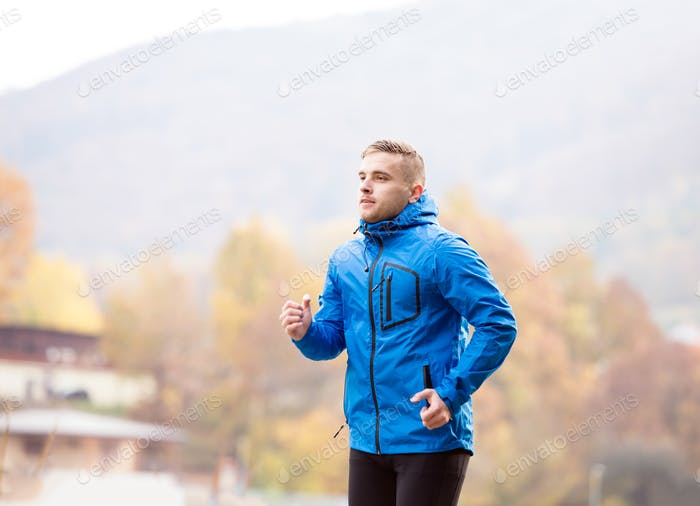 Young athlete in park running in colorful autumn nature