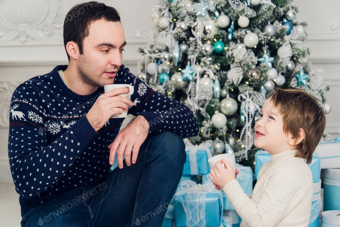 Father with his son sitting relaxed in ski resort chalet and drinking hot tea, joyful winter