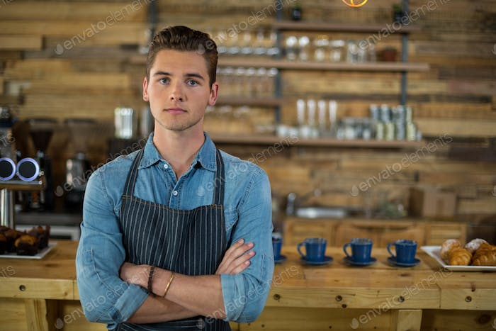 Waiter standing with arms crossed in cafe