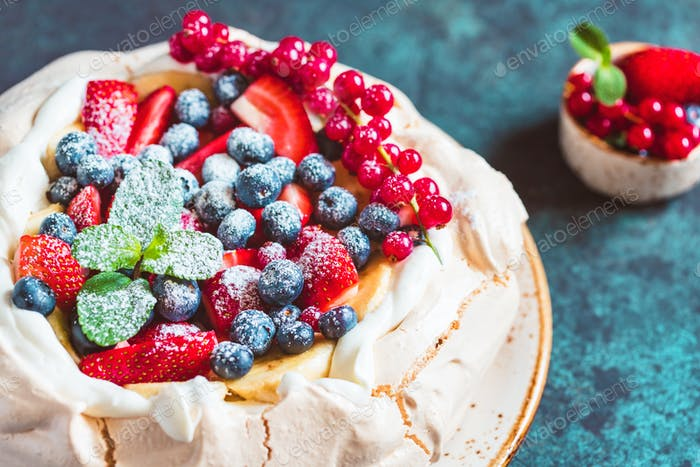 New Zealand Pavlova cake with whipped cream and mix of fresh berries on a blue textured background.