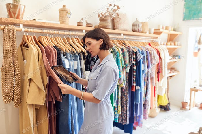 Female Owner Of Fashion Store Using Digital Tablet To Check Stock On Rails In Clothing Store