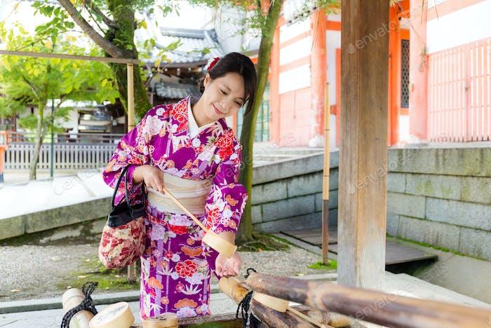 Japanerin benutzt die Wasser-Bambuskelle zur Reinigung