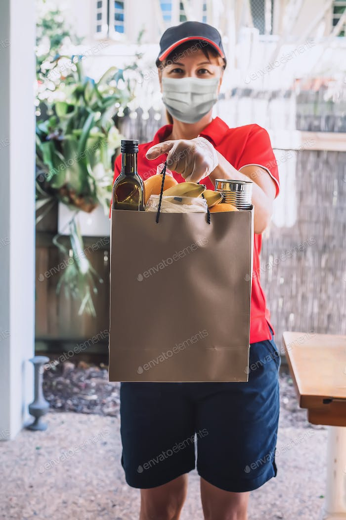 Delivery woman in protective face mask and gloves delivers paper bag with food products.