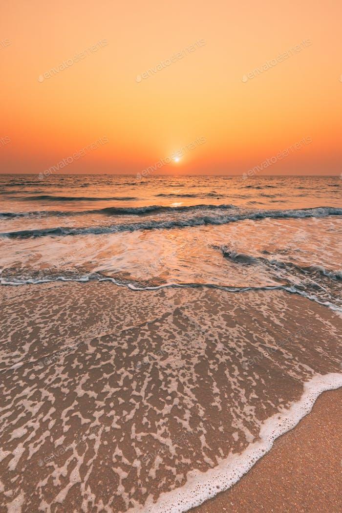 Sunset Sun Above Sea. Natural Sunrise Sky Warm Colors Over Ripple Sea. Ocean Water Foam Washing