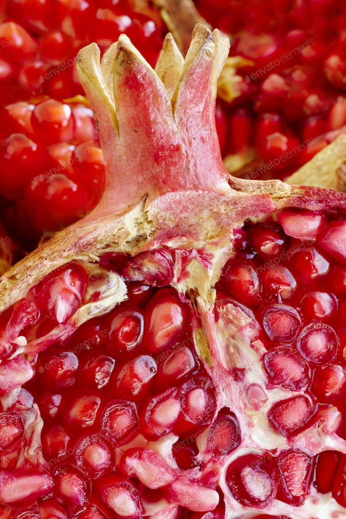 Pomegranate fruit seeds macro detail. Healthy food. Vertical