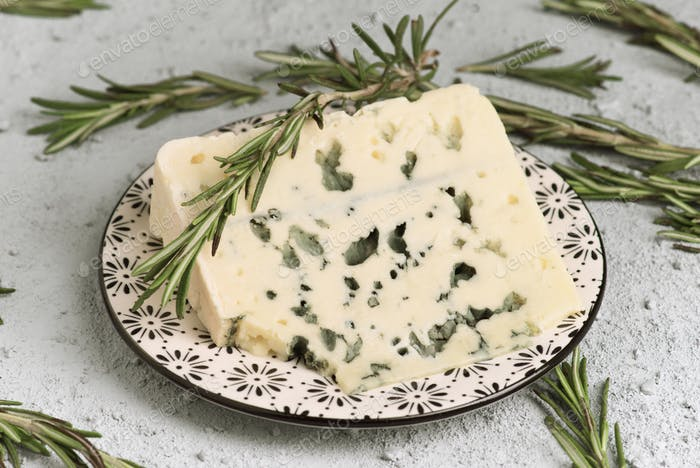 piece of roquefort cheese on plate decorated with rosemary on rustic granulated background