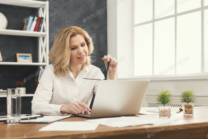 Serious businesswoman working on laptop at office