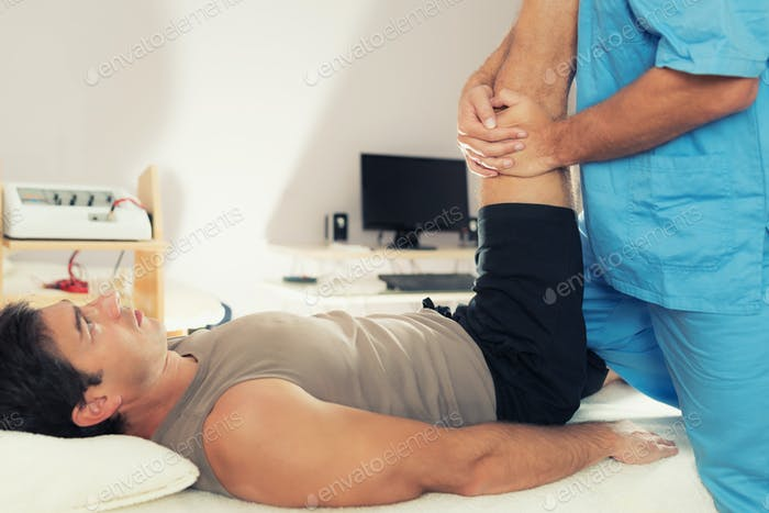 Physiotherapist Working With Patient Leg