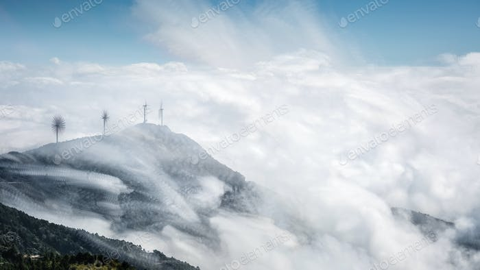 mountain top of wind farms with clouds