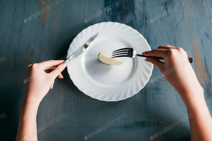 Weibliche Person gegen Teller mit einer Scheibe Apfel