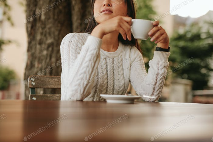 Junge Frau hält eine Tasse Kaffee im Café