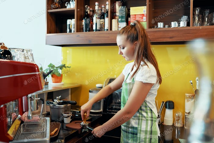 Woman preparing coffee with tamper